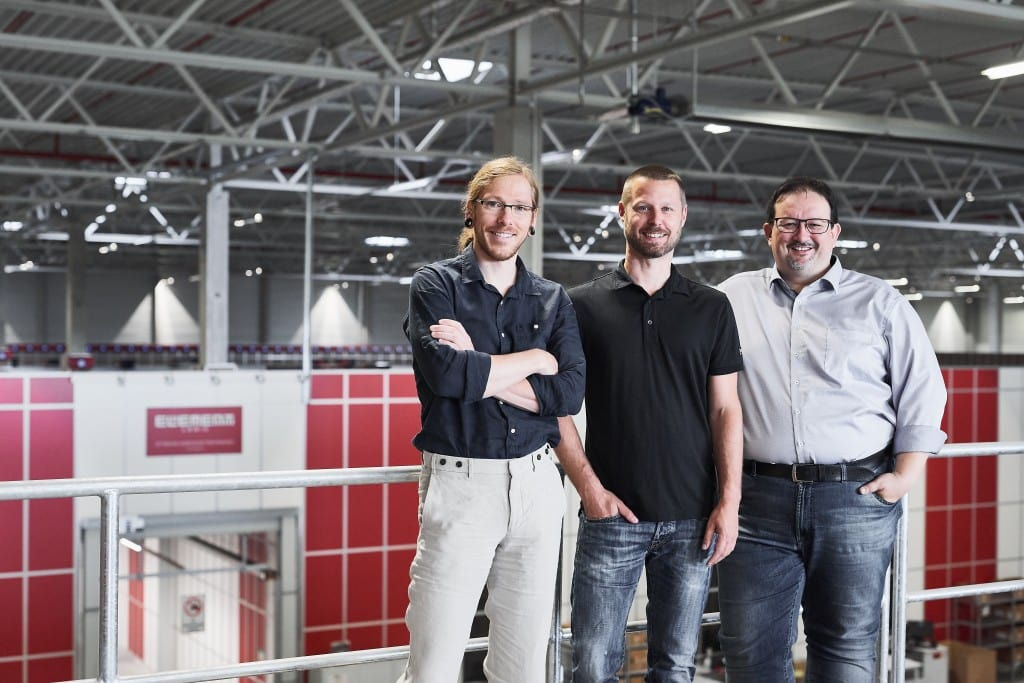 Thomas Klein and Ronny Höhn from Bergfreunde and Michael Kawalier from Element Logic i front of AutoStore grid