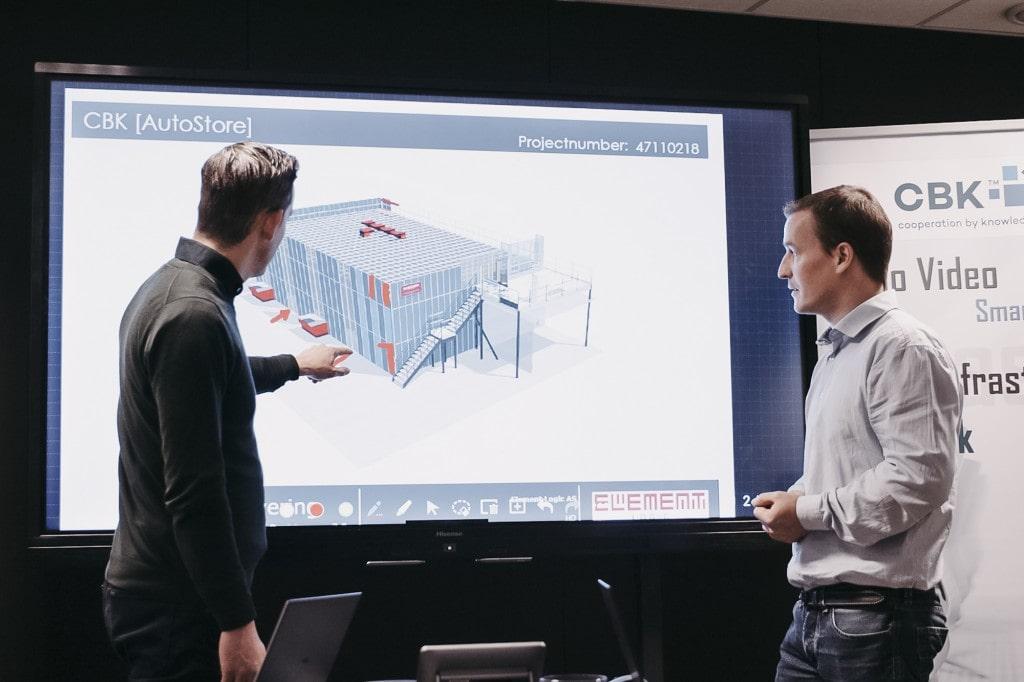 Zwei Männer zeigen auf eine Präsentation, die die Zeichnung einer AutoStore-Lösung enthält.
