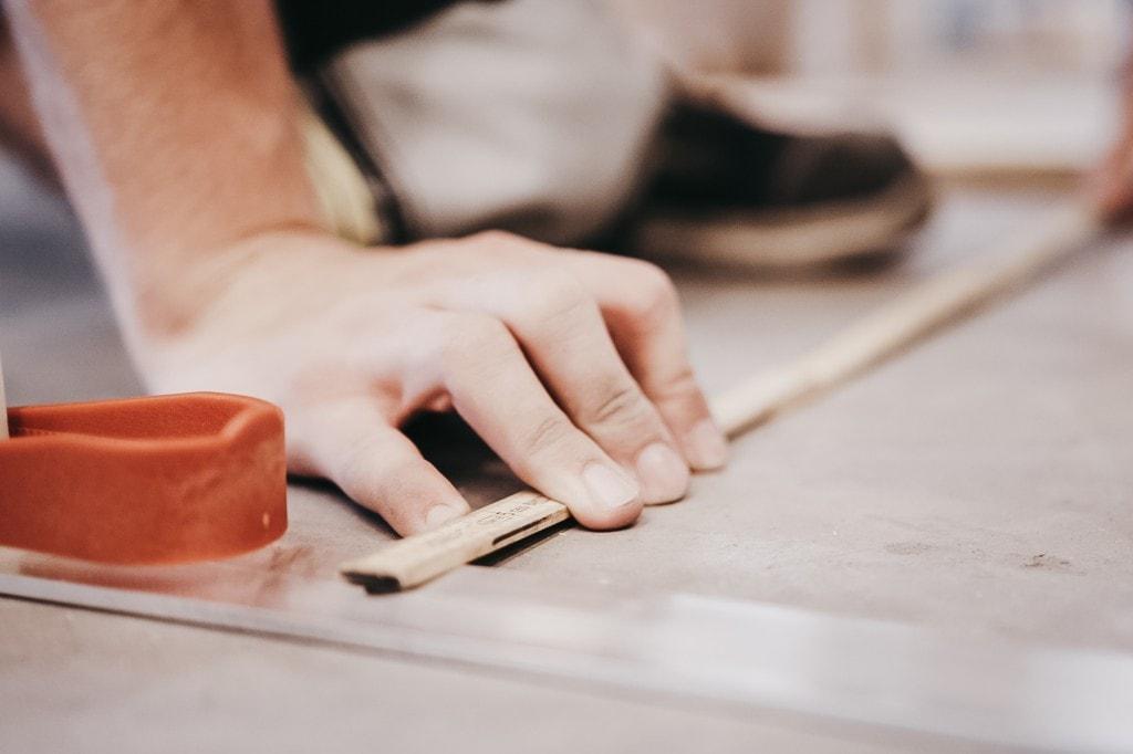 Ein Paar Hände misst mit einem Meterstab die Abstände der Aluminiumsäulen des AutoStore-Rasters.