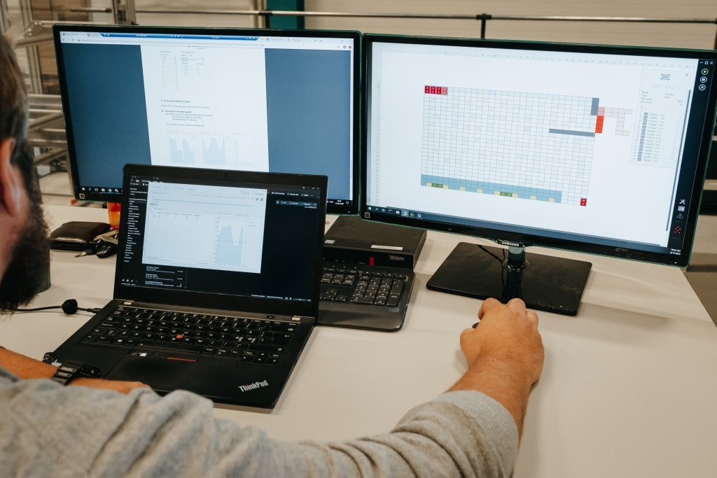 Ein Mann arbeitet mit drei Bildschirmen an einer AutoStore-Lösung.