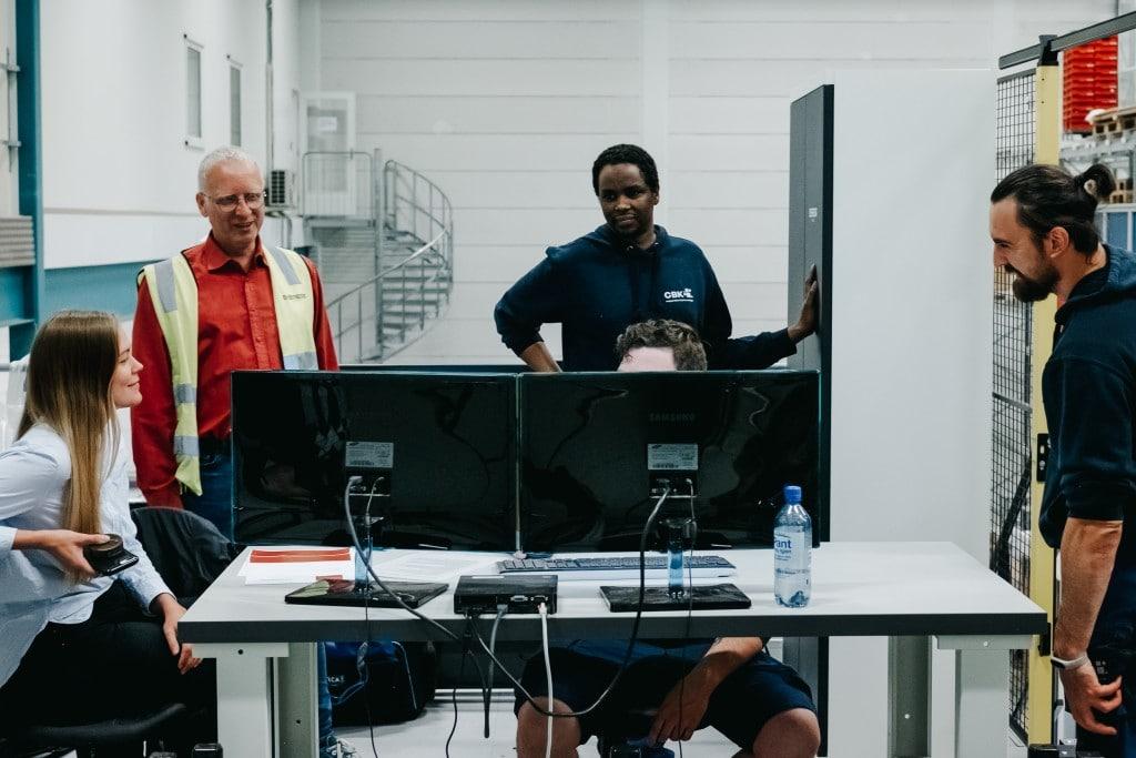 Fünf Personen arbeiten vor einem Computer zusammen, um die Bedienung des AutoStore-Systems zu erlernen.