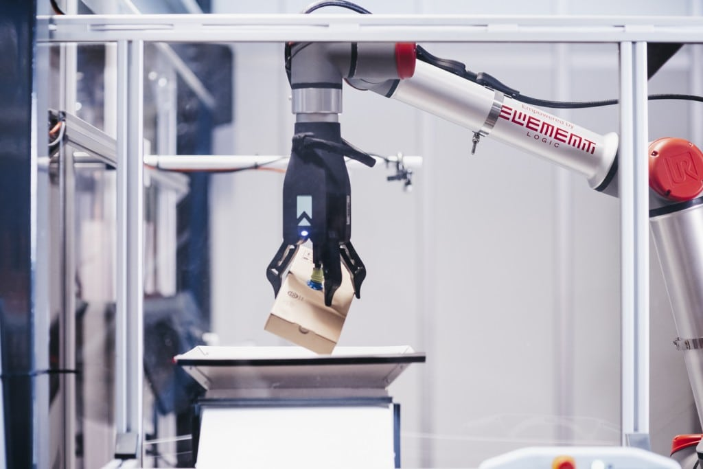Robot arm picking brown box from AutoStore